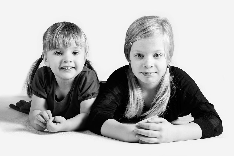 Portræt af to piger liggende på gulvet på hvid baggrund af palle christensen