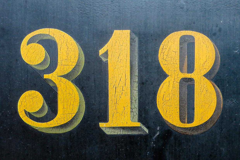 Ældre tognummer skilt tæt på med detaljer af Palle Christensen