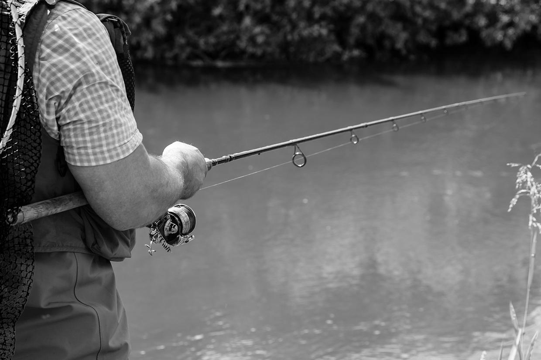 Lystfisker der fisker ved vandet i sort hvid af palle christensen