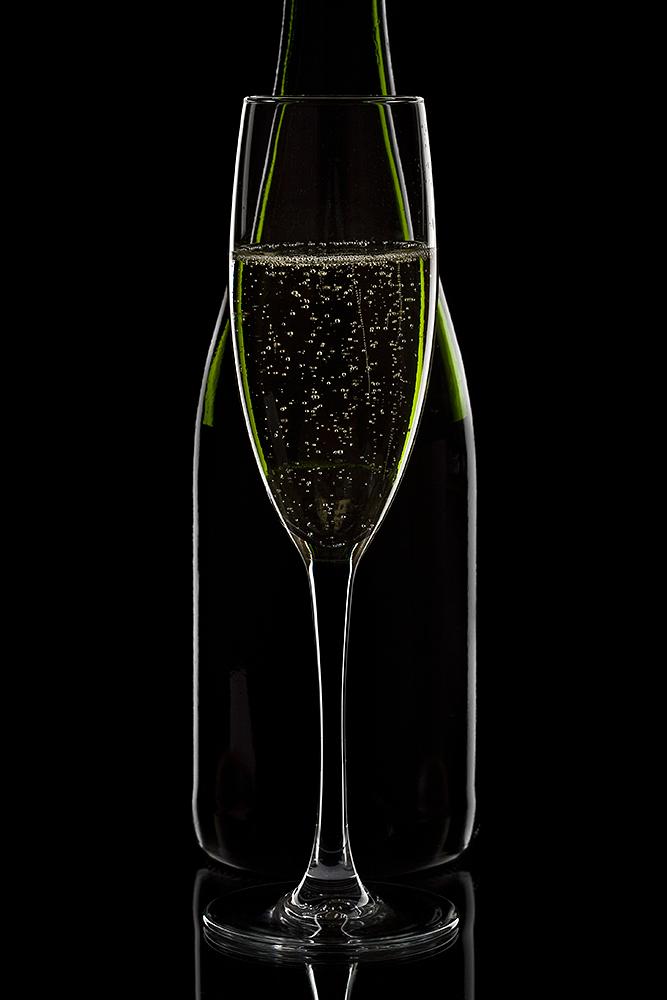 Fyldt champagneglas med flaske bagved på sort baggrund